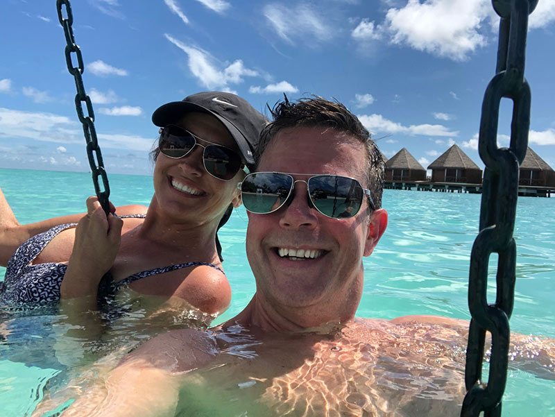 Couple on a swing in the water at Mercure Maldives Kooddoo resort all inclusive